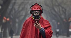 תושב סין עם מסיכה בעקבות התפרצות הנגיף, צילום: גטי אימג'ס