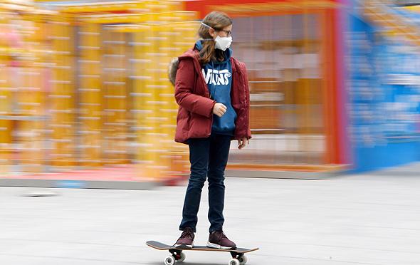 בייג'ינג נערה על סקייטבורד עם כיסוי פנים