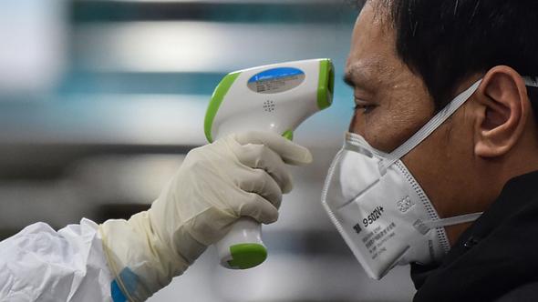 מדידת חום לאדם בסין בשל נגיף הקורונה, צילום: איי אף פי
