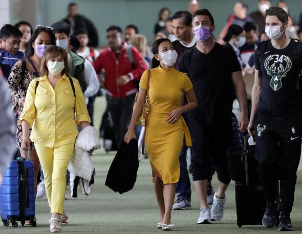 אנשים עם מסכות בנמל התעופה בפיליפינים