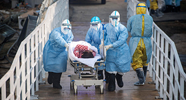 A coronavirus patient being led into hospital. Photo: AP