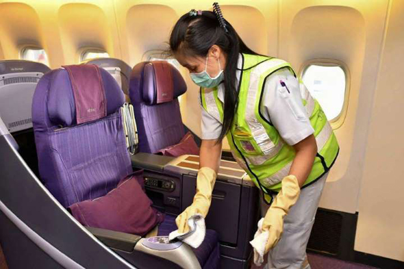 An employee sterilizes the seats on a plane. Photo: AFP