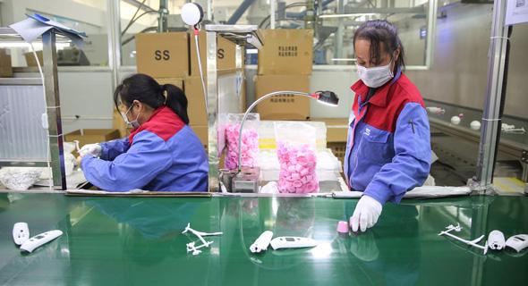 קורונה עובדים המייצרים מדי חום במפעל במחוז שאנדונג בסין