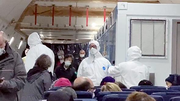 """אמריקנים על המטוס שפינה אותם השבוע לארה""""ב מספינת הקורונה, צילום: איי פי"""