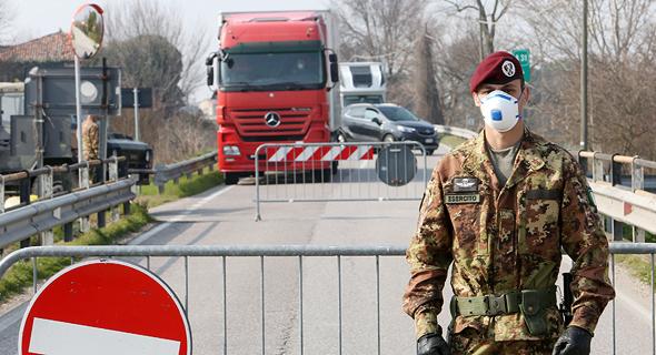 חייל שומר על איזור באיטליה שנמצא בבידוד בעקבות הקורונה