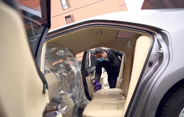 נהג של דידי בבייג'ינג מחטא את רכבו