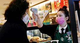 מוכרת בסניף של סטארבקס בסין בודקת חום ללקוחה, צילום: רויטרס