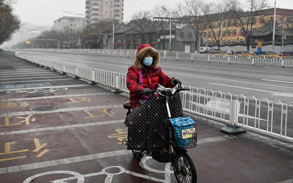 אשה על אופניים עם מסיכה בבייג