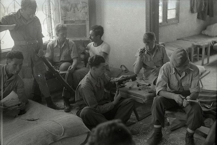 חיילי ההגנה מנקים את נשקם בבית נטוש במהלך הקרבות, צילום: אוסף בנו רותנברג
