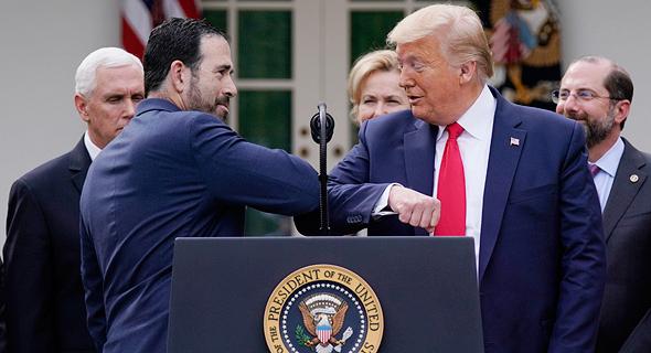 """נשיא ארה""""ב  דונלד טראמפ מתרגל """"נגיעת מרפקים"""" במקום לחיצת יד במסיבת עיתונאים בבית הלבן, שלשום, צילום: איי פי"""