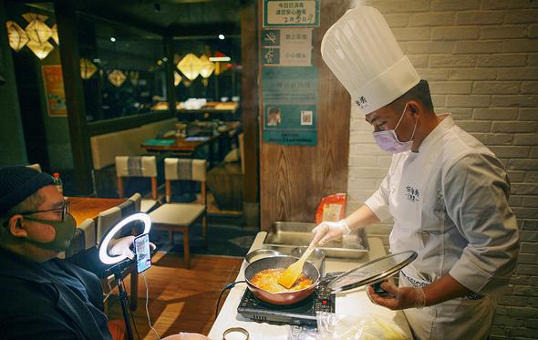 שף עטוי מסכה בעיר טיניאן בסין מעביר שיעור בישול מקוון במסעדה הריקה. המילניאלז שנאלצו לוותר על משלוחי מזון, החלו ללמוד לבשל, צילום: רויטרס