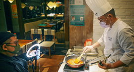 שף עטוי מסכה בעיר טיניאן ב סין מעביר שיעור בישול מקוון ב מסעדה ריקה פנאי, צילום: רויטרס