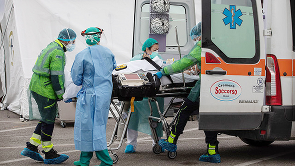 A coronavirus patient is led into an ambulance. Photo: Getty Images