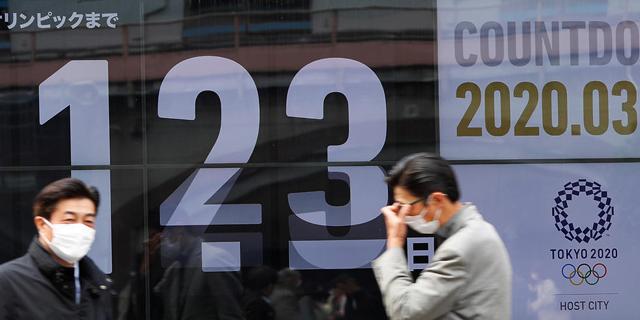 אזרחים בטוקיו על רקע שלט של האולימפיאדה, צילום: רויטרס