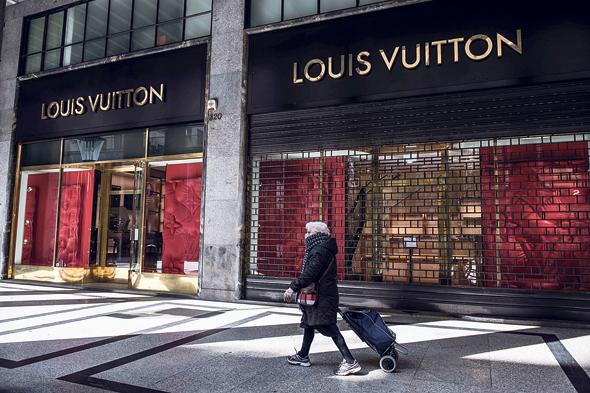 אשה חולפת על פני חנות סגורה של ויטון בטורינו, איטליה. LVMH תרכוש 40 מיליון מסכות מסין עבור בתי חולים בצרפת