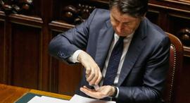 ראש ממשלת איטליה ג'וזפה קונטה מחטא את ידיו אחרי נאום בפרלמנט, צילום:  EPA