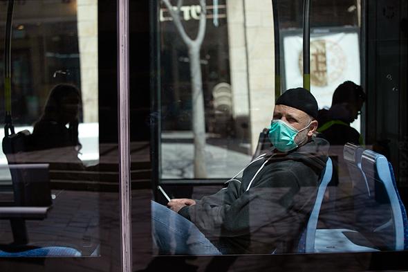 A man wearig a mask on a bus in Jerusalem. Photo: Amit Shabi