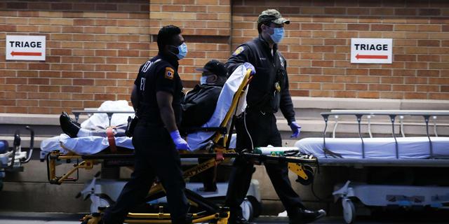 שוטרים מעבירים חולה קורונה בניו יורק, צילום: איי אף פי