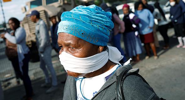 תושבת קייפטאון, דרום אפריקה, מתגוננת מפני נגיף הקורונה