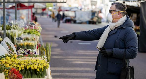 אדם רוכש פרחים בשוק הפרחים באמסטרדם הולנד , צילום: אי פי איי