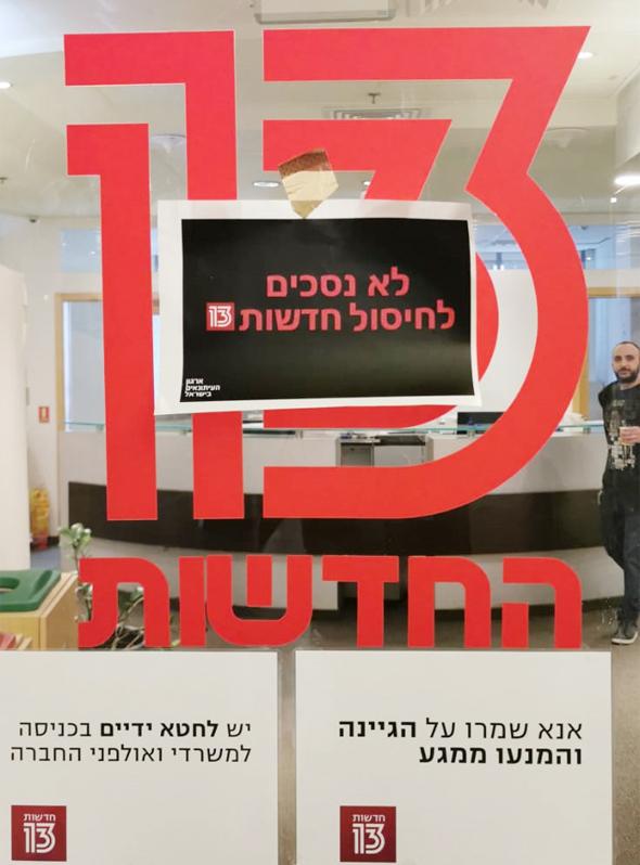"""שלט מחאה בדסק של חדשות 13, צילום: יח""""צ"""