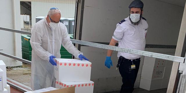 פרופ׳ רוברט פלור מנהל המרכז הישראלי הלאומי לרפואה מקבל את המשלוח הראשון של בדיקות הקורונה, צילום: מכון ויצמן למדע