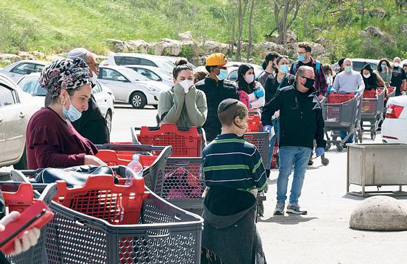 Shoppers line up outside a supermarket. Photo: Amit Shabi
