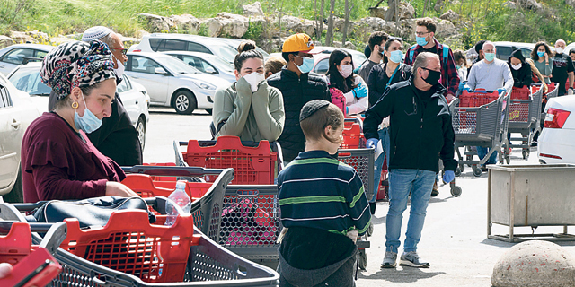 Shoppers line up outside a supermarket in March 2020. Photo: Amit Shabi