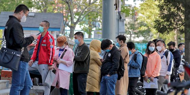 עובדים ממתינים לבדיקת חום במגדל משרדים בבייג