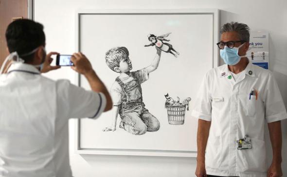 אנשי צוות בבית החולים מצטלמים עם היצירה של בנקסי, צילום: איי פי