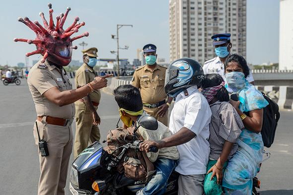 """שוטר בהודו עם """"קסדת קורונה"""" מזהיר תושבים להיכנס לבידוד"""