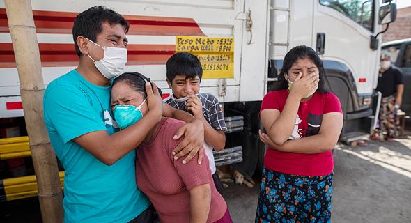 משפחה מתאבלת בלוויה של חולה קורונה בלימה, פרו