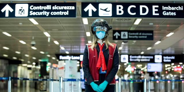 דיילת עם קסדה למדידת חום בנמל התעופה ברומא, צילום: איי פי