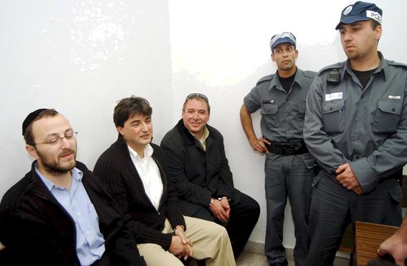 יושבים מימין: אמסלם עם חברי הקבוצה הירושלמית יורם קארשי ויצחק קויפמן בעת מעצרם ב־2003 בחשד לזיוף מסמכים כדי לגייס מתפקדים חדשים לליכוד