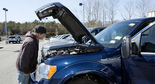 לקוח בודק רכב משומש במגרש של CarMax