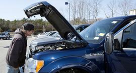 לקוח בודק רכב משומש במגרש של CarMax, צילום: בלומברג