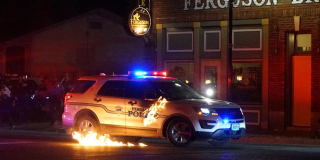 מכונית משטרה עולה באש במיניסוטה, צילום: רויטרס