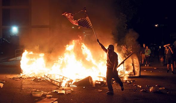מפגין בסנט לואיס שורף את הדגל האמריקאי במחאה על מותו האלים של ג'ורג' פלויד