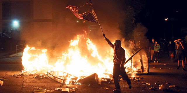 מפגין בסנט לואיס שורף את הדגל האמריקאי במחאה על מותו האלים של ג