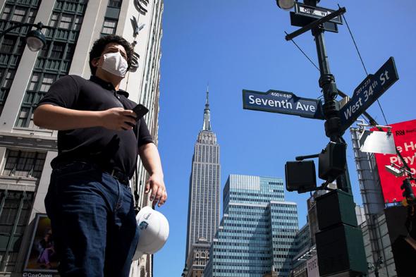 תושב ניו יורק על רקע אמפייר סטייט בילדינג בזמן משבר הקורונה