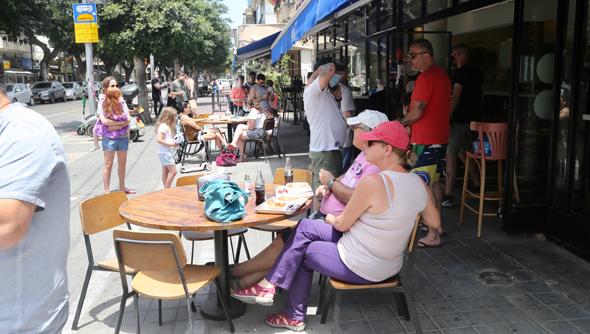 אנשים יושבים מחוץ למסעדת סוס אנד סאנס בתל אביב