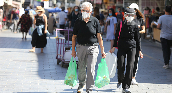 People wearing face masks in Jerusalem. Photo: Alex Kolomoisky‎