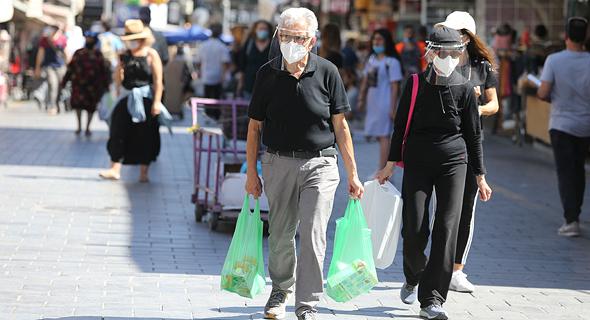 People wearing face masks in Jerusalem. Photo: Alex Kolomoisky