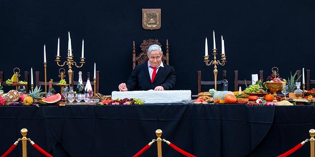 """מיצב בת""""א: נתניהו אוכל פרוסה מעוגת דגל ישראל"""