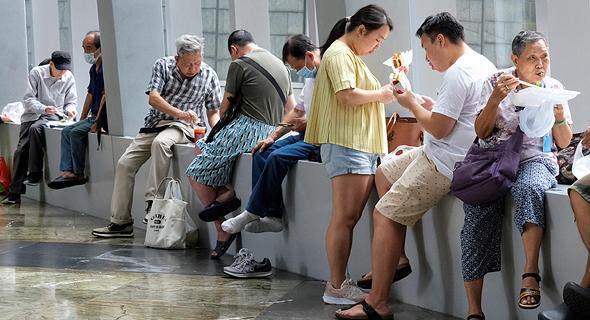 עובדים בהונג קונג אוכלים על המדרכות לאחר שהמסעדות נסגרו לישיבה, צילום: רויטרס
