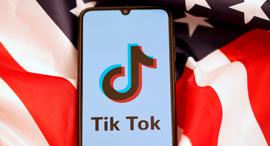 """אפליקציית טיקטוק על רקע דגל ארה""""ב, צילום: רויטרס"""