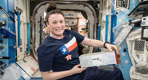 An astronaut at the ISS holding one of SpacePharma