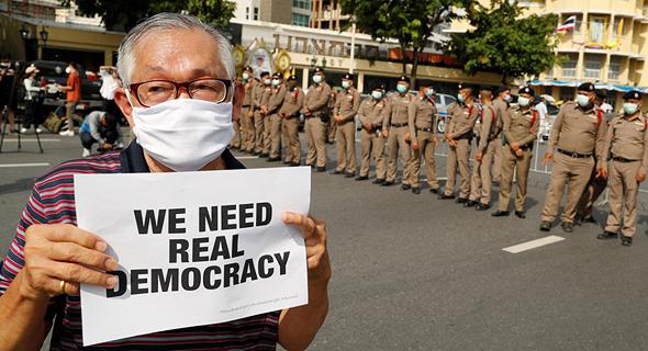 """מפגין נושא שלט ועליו הכיתוב - """"אנחנו זקוקים לדמוקרטיה אמיתית"""", צילום: רויטרס"""