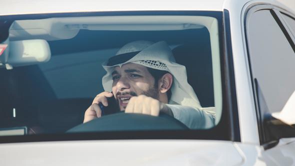 אדם מדבר בסלולרי ברכב, איחוד האמירויות, צילום: שאטרסטוק