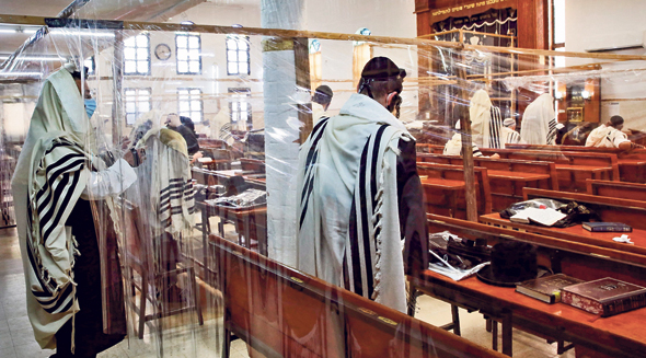 Jewish worshipers praying in an Israeli synagogue separated by nylon Covid-19 barriers during the High Holidays. Photo: AFP